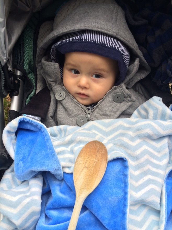 Baby in stroller with wooden spoon