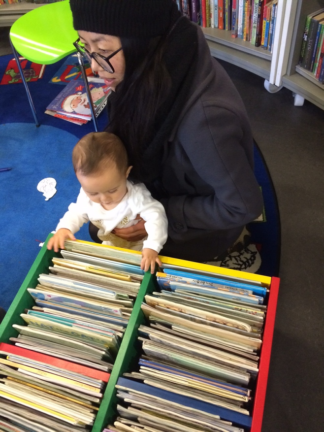 Baby looking at boxes of books