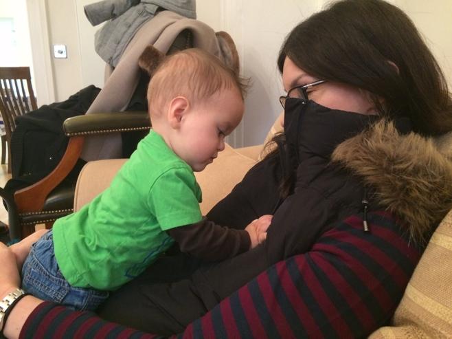 Baby on woman on sofa