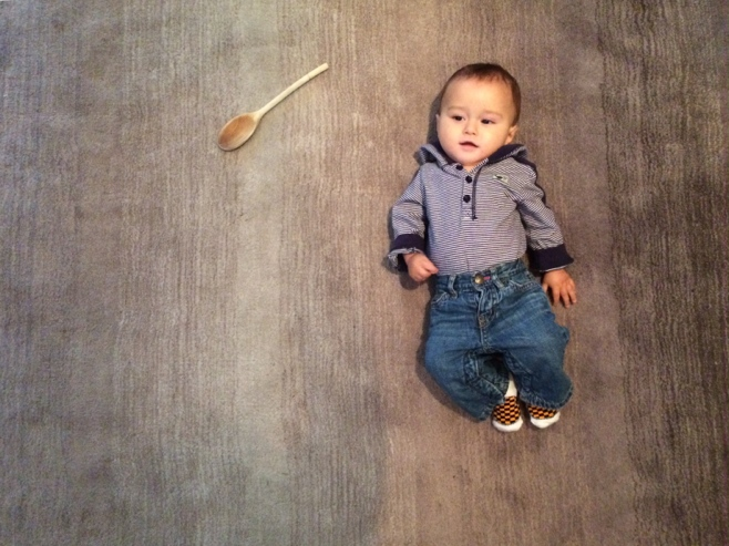 Baby on grey carpet with wooden spoon