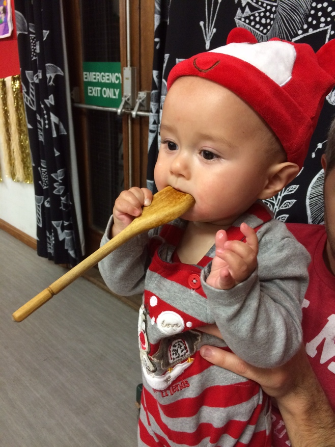 Baby playing with a wooden spoon