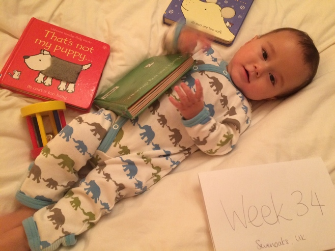 Baby reading books in bed