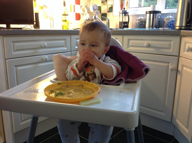 Baby in high chair stuffing his face