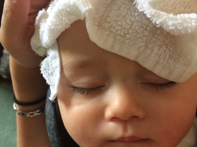 Baby with cold towel on head