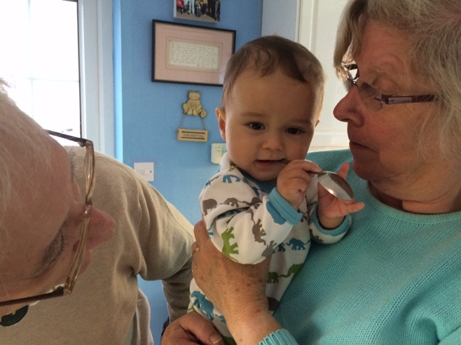 Baby with silver spoon and grandparents