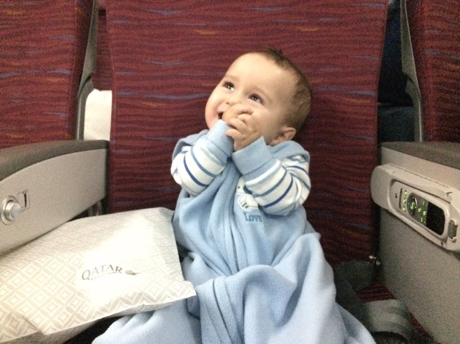 Baby in airplane seat clapping hands
