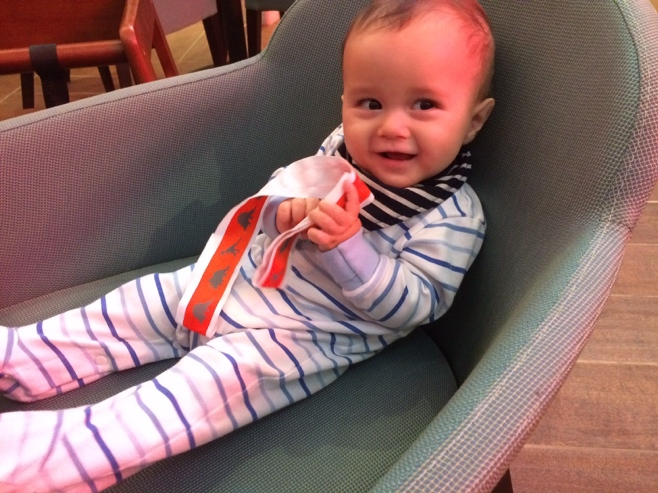 Baby playing with orange strap