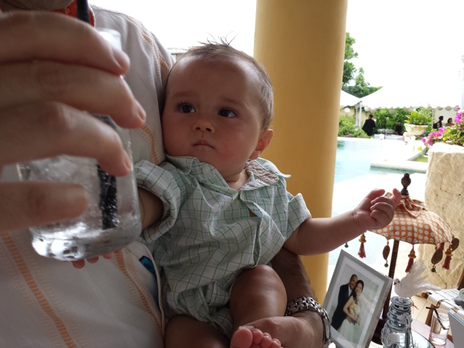 Baby reaching for dad's drink