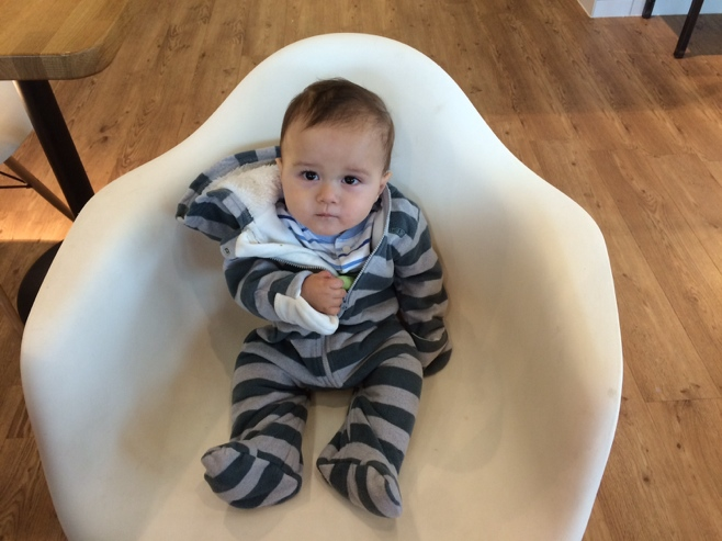 Baby sitting in white chair