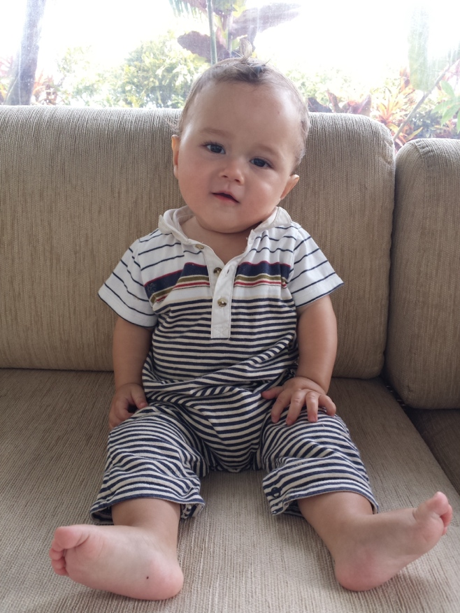 Baby in stripped outfit sitting on a couch