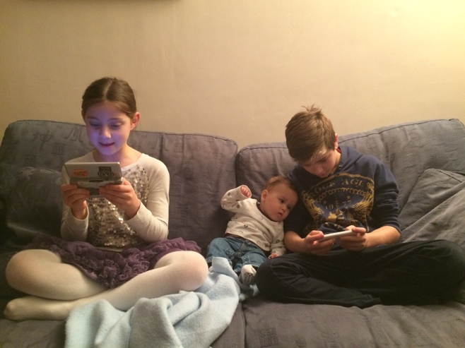 Kids and baby on sofa playing video games