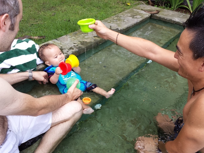 Baby holding two pots in swimming pool with dad and friend