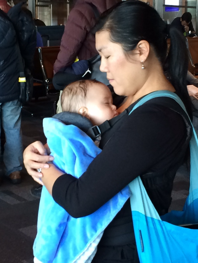Mum carrying baby wrapped in blue blanket