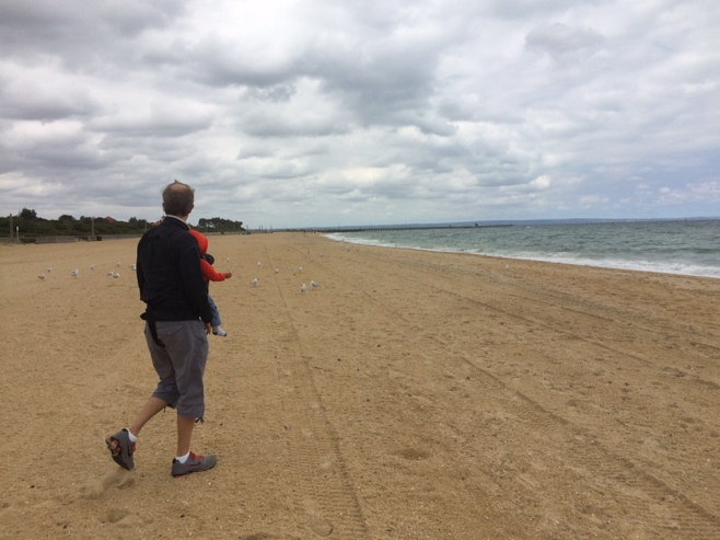 Man and baby on beach with segues in the background
