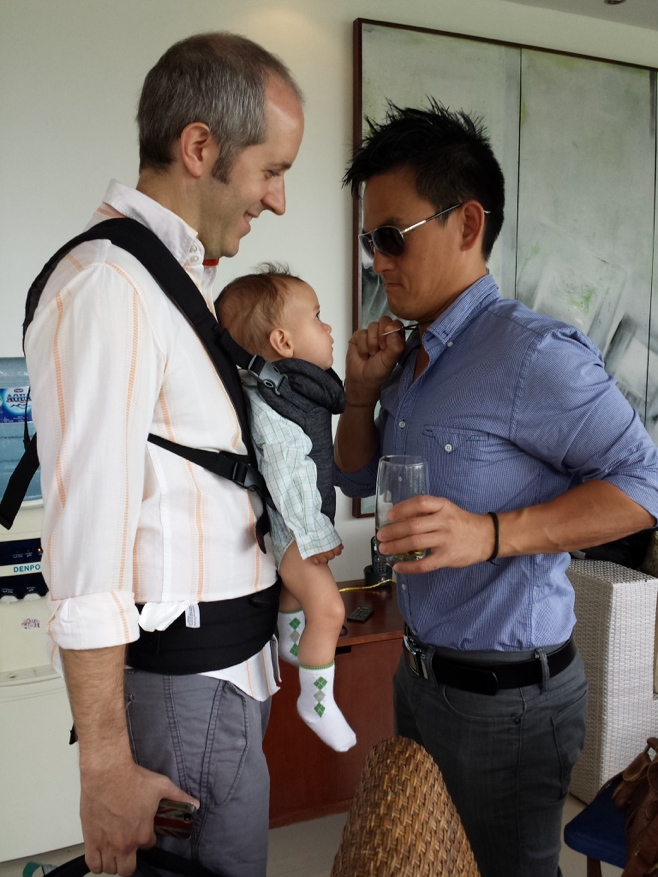 Baby in carrier looking at mans necklace