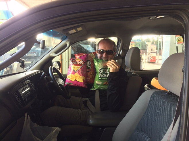Man in car holding bags of chips