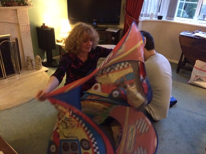 Two adults trying to fold up play tent