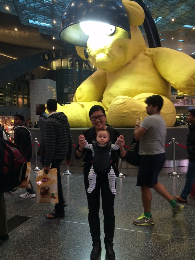 Posing in front of a giant yellow teddy bear at Doha airport