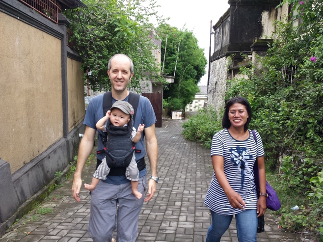Dad carrying baby and babysitter walking
