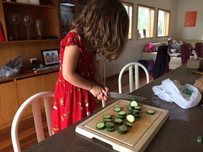 Little girl cutting cucumber