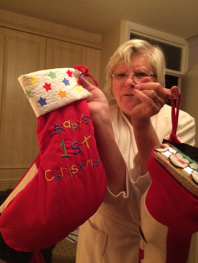 Grandma holding Christmas stocking for baby