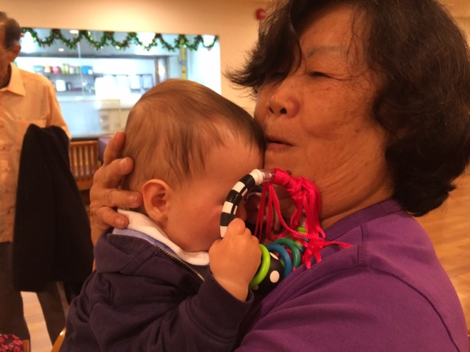 Baby holding rattle cuddling great aunt