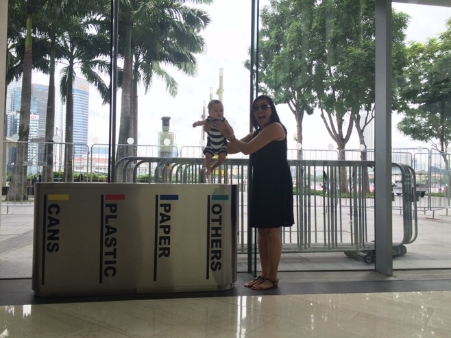 Baby held over trash can
