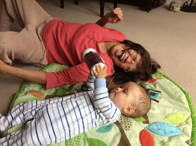 Grandma lying on play mat with baby