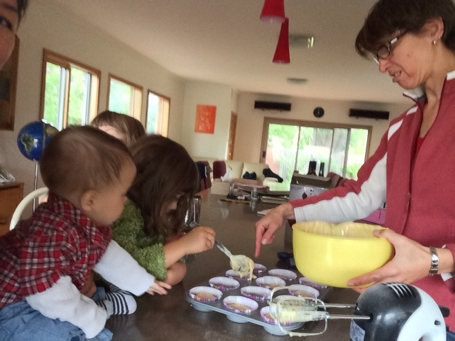 Woman making cupcakes with kids looking on