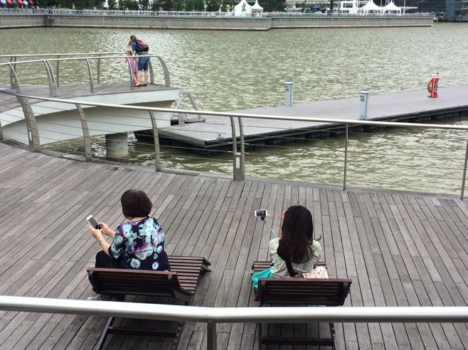 women with selfie sticks