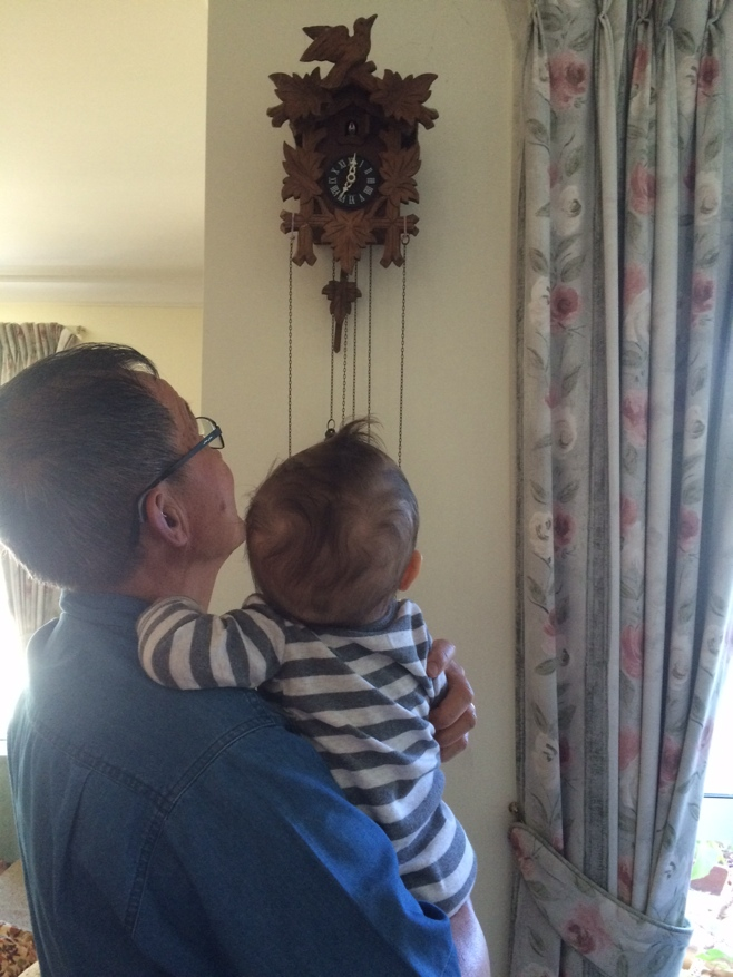 Baby and uncle looking at cuckoo clock