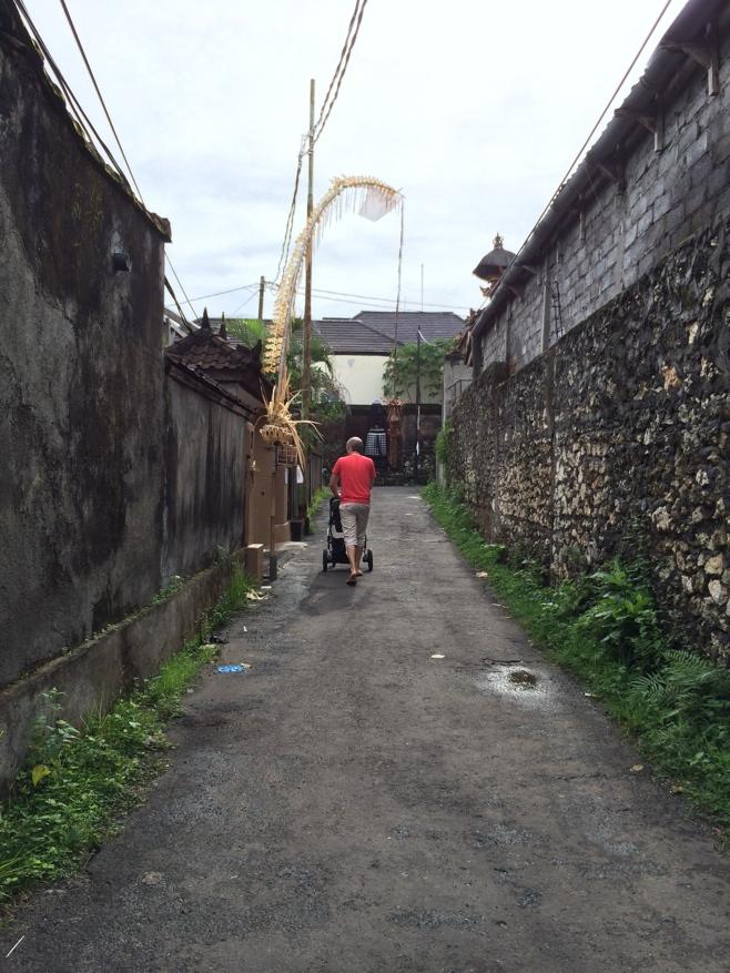 Man pushing stroller down lane in Bali