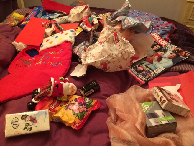 Wrapping paper and gifts all over the bed