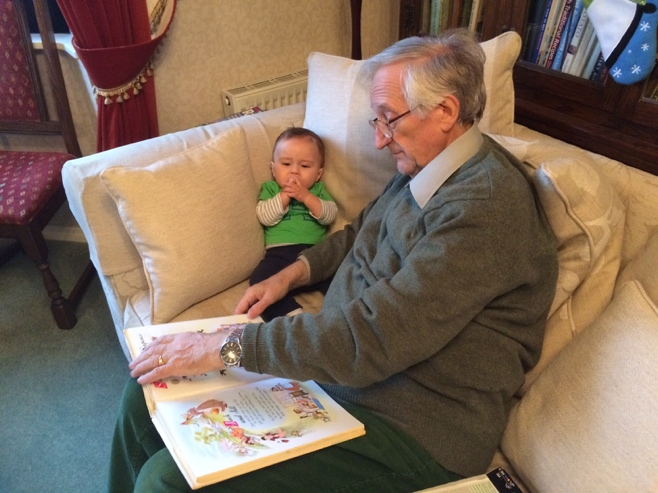 Grandpa reading nursery rhymes to baby