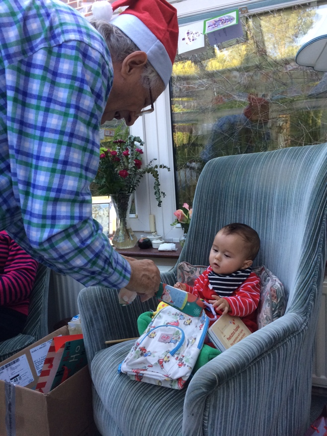 Grandpa giving baby a present