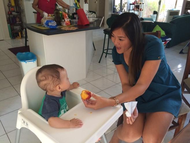 Auntie feeding baby a nectarine