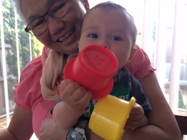 Baby playing with buckets held by Aunty