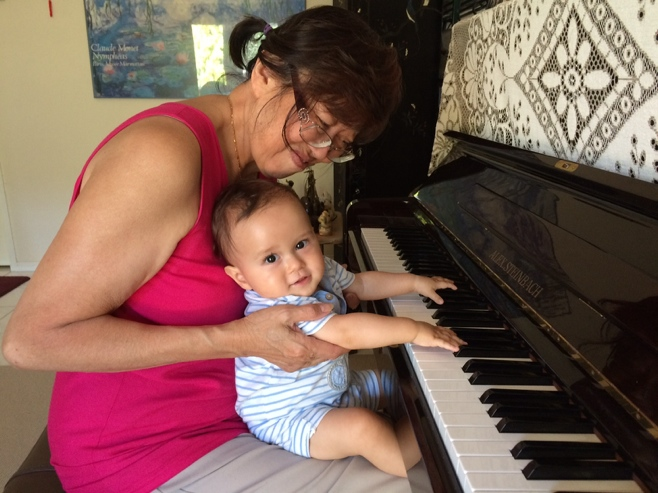 Baby and grandma playing the piano