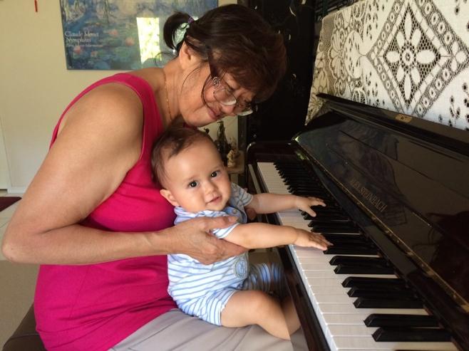 Baby and grandma playing the piano