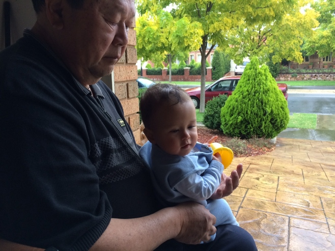 Grandpa and baby watching the rain