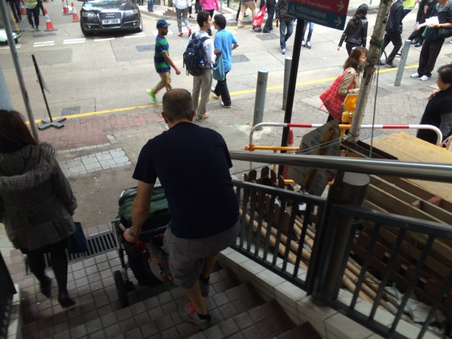 Man lifting stroller down stairs