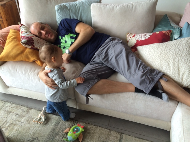 Man lying on couch and baby standing nearby