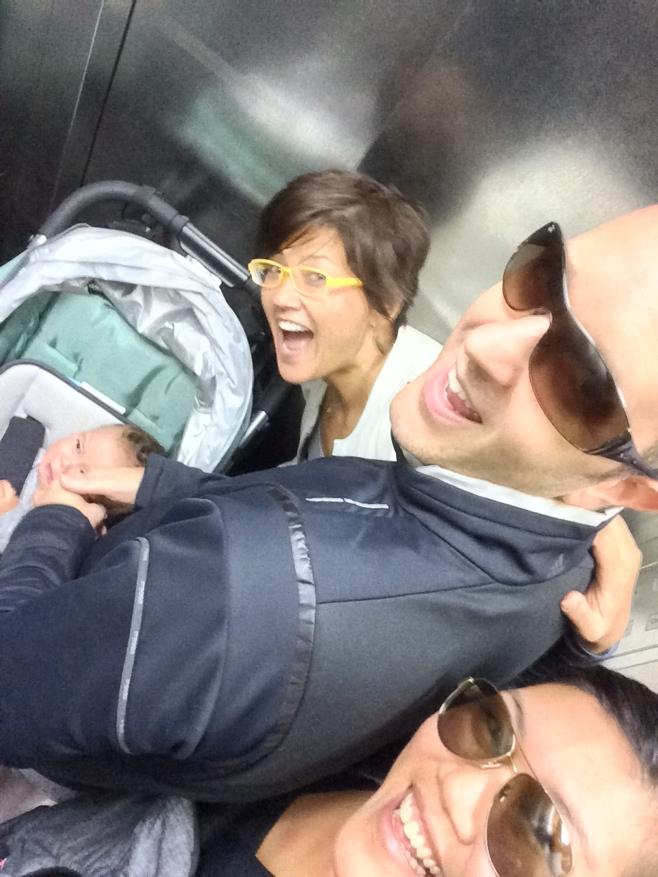 Three people and baby in group elevator selfie
