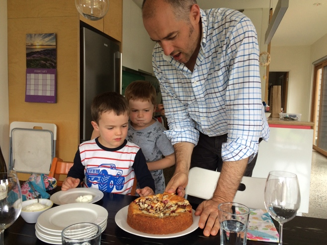 Dad cutting up a plum cake with boys looking on