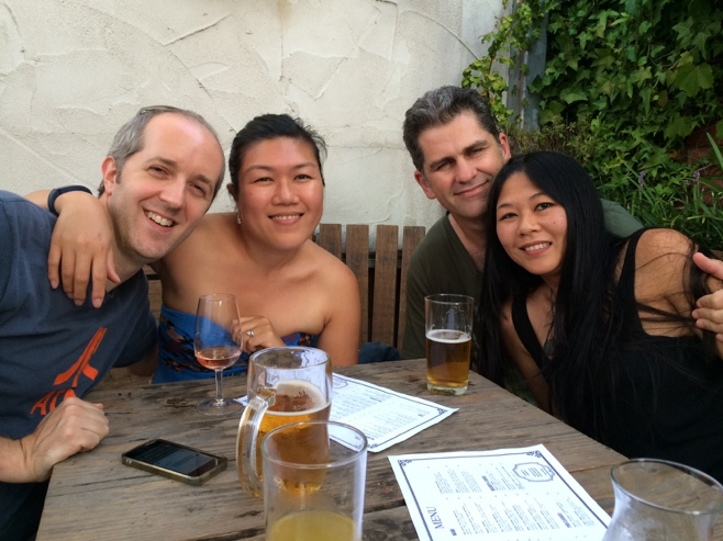 Two couples having a beer outdoors