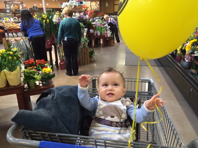 Baby in shopping cart with yellow helium balloon