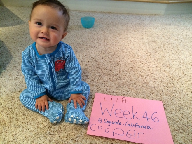 Baby sitting on carpet with sign that says week 46