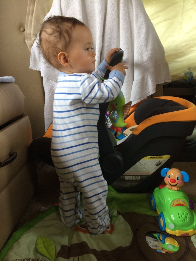 Baby standing against car seat