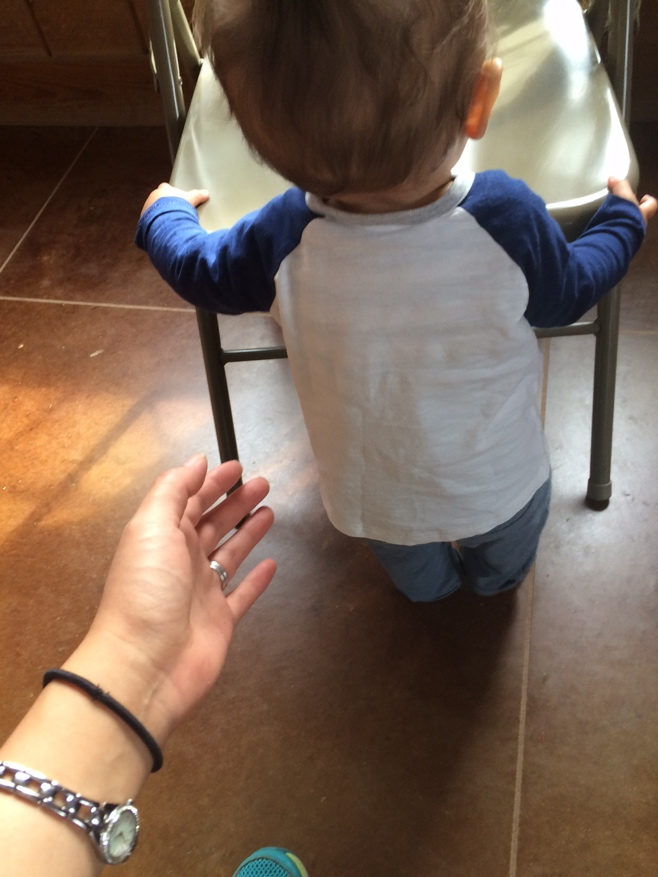 Baby holding onto chair and trying to walk