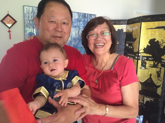 Baby in Chinese outfit with grandparents in red